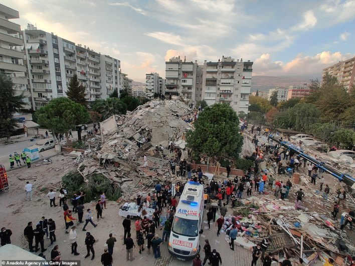 An aerial vivew of a pile of rubble in Turkey with dozens of rescuers and emergency workers on the scene as the light faded