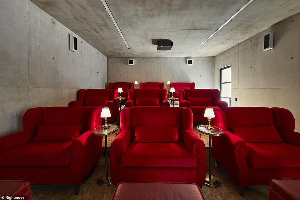 A pop of blood red: Most of the interiors are finished in concrete, including  the home cinema