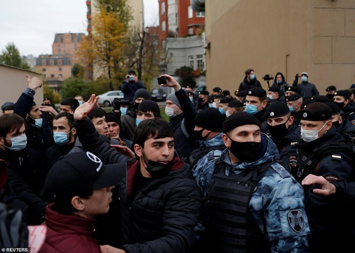 Demonstrators stand in front of Russian law enforcement officers during a protest against the publications of a cartoon of Prophet Mohammad in France