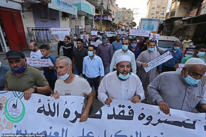 Palestinians in Gaza carry banners during a protest against Macron in the enclave on Friday as Muslims around the world gathered to decry Macron's defence of cartoons depicting the Prophet Muhammad