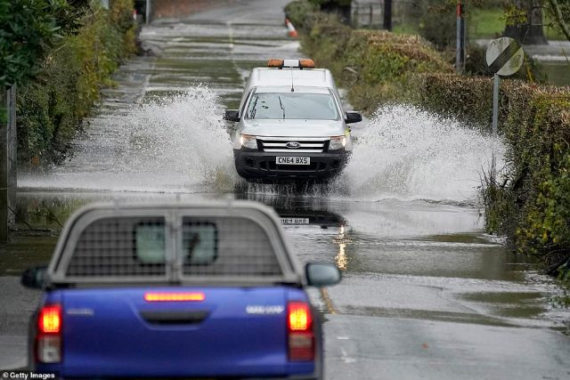 Cars drive on a flooded road as the River Conwy bursts its banks yesterday in Llanrwst, Wales, on Thursday