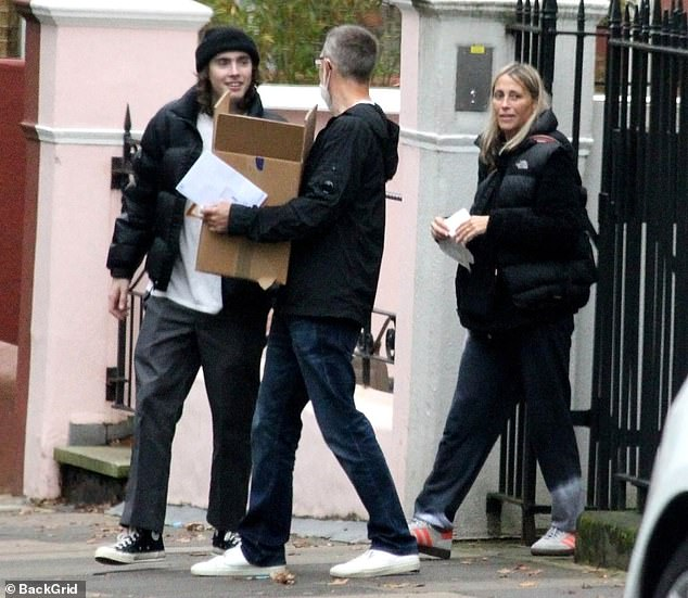 Family effort: The All Saints star left the property holding two pairs of trainers and a bucket of sweets in her arms, while her beau carried a cardboard box full of goods