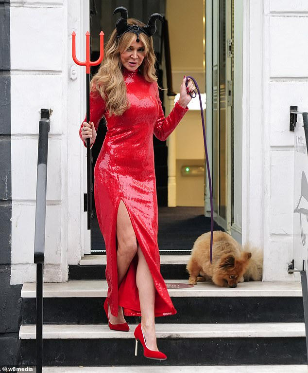 Racy: Her scarlet number featured a daring thigh-high split which revealed her slender pins as she walked down stairs with her adorable pooch in tow