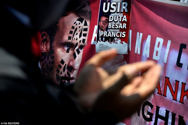 A placard and banner depicting French President Emmanuel Macron are seen during a protest against Macron's comments considered insulting to Muslims, in Makassar, South Sulawesi Province, Indonesia today