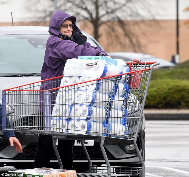In similar scenes to the first wave in March, people in United Kingdom were seen stocking up on toilet roll as they prepared for a new lockdown (pictured, a shopper at Costco, Manchester)