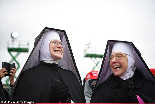 Dominican Sisters of Hartland, Michigan, watch as US President Donald Trump arrives to speak at a 'Make America Great Again' rally at Oakland County International Airport