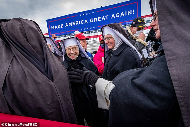 The Dominican Sisters of the Immaculate Heart of Mary of Hartland, Michigan, speak amongst themselves while attending President Trump's rally in Waterford Township