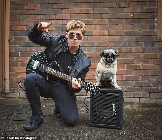 'Rock on, this Halloween': Robert Irwin, 16, channelled his inner rock star for his Halloween costume dressed in all black, with a leather jacket and aviator sunglasses.He also teamed his outfit with an electric guitar and an amplifier, and posed with his pet dog Stella.