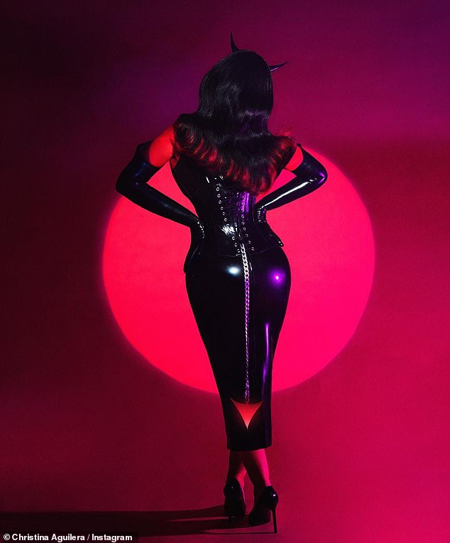 Fierce:The singer appeared in three retro, stylized portraits, bathed in red light while wearing a skintight sleeveless PVC midi dress complete with a chain link devil's tail and black horns