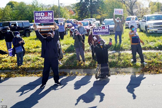 Roadside support: Supporters were on show outside the high school in Flint where the former president and would-be next president were appearing together - including one in Halloween costume