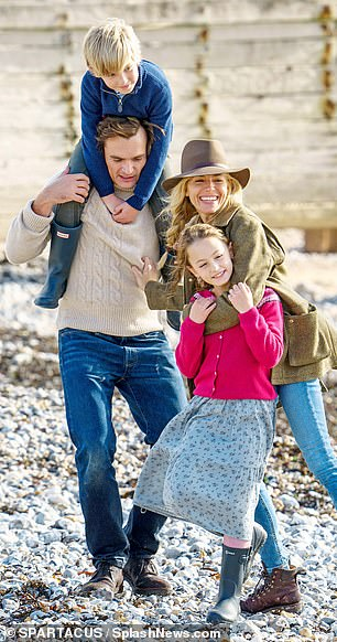At first glance, it could be any good-looking family enjoying a day out by the sea. But a closer look reveals it is Hollywood stars Sienna Miller and Rupert Friend strolling on an East Sussex beach with two child actors