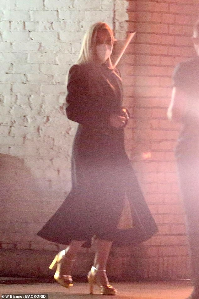 Stylish:Hudson was dressed up in a lovely yellow dress and dark long coat for the shoot, along withmetallic gold heeled sandals which glinted in the light