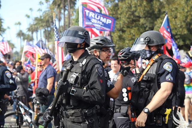 Cops in Beverly Hills form a skirmish line to keep competing groups of protesters separate on Saturday