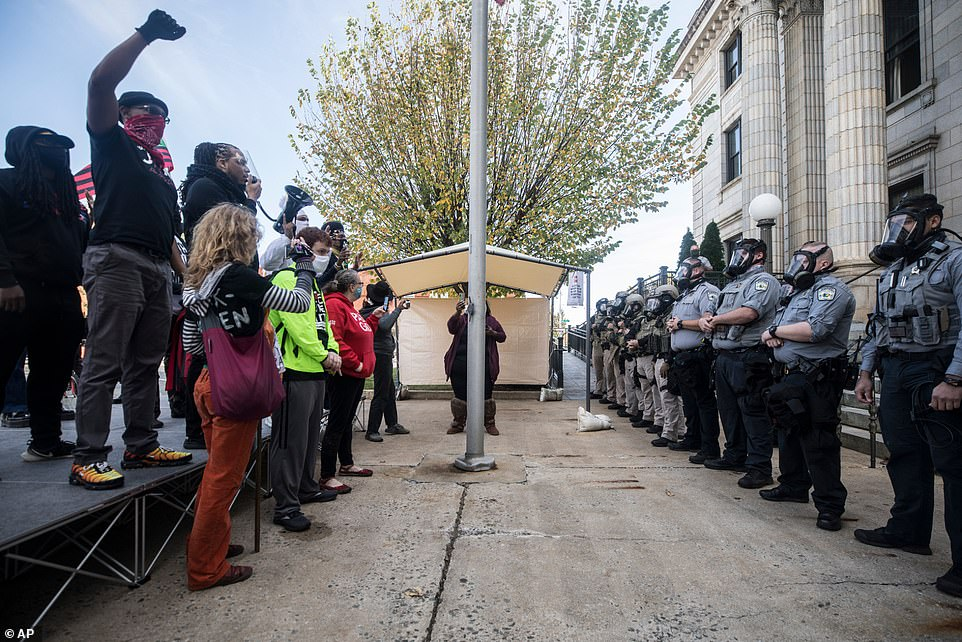 BLM demonstrators and Alamance County sheriff's deputies in riot gear face off in front of the courthouse in Graham, North Carolina on Saturday, Oct. 31, 2020 before pepper spray was used and several people were arrested