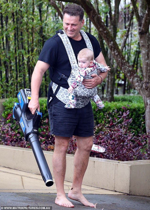 Multi-tasking: A barefoot Karl was spotted clutching a leaf blower outside his Sydney home, as Harper watched on from her leopard-print baby sling