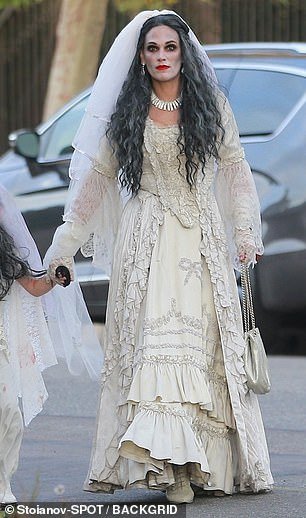 All white: She wore a long sheer white veil over a wavy grey wig, completing the look with a white choker and matching heels