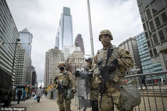 National Guard members patrol the area around Philadelphia City Hall on October 30 in Philadelphia, Pennsylvania, in response to widespread unrest in the aftermath of a police shooting