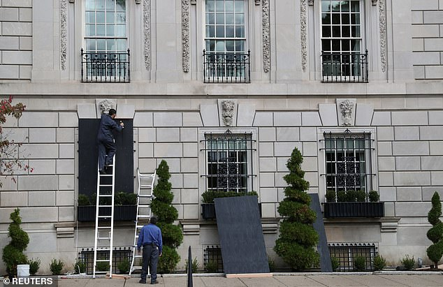 Businesses across major cities in the US have been boarded up in anticipation of riots (Workers pictured at The Hay-Adams hotel across the street from the White House)