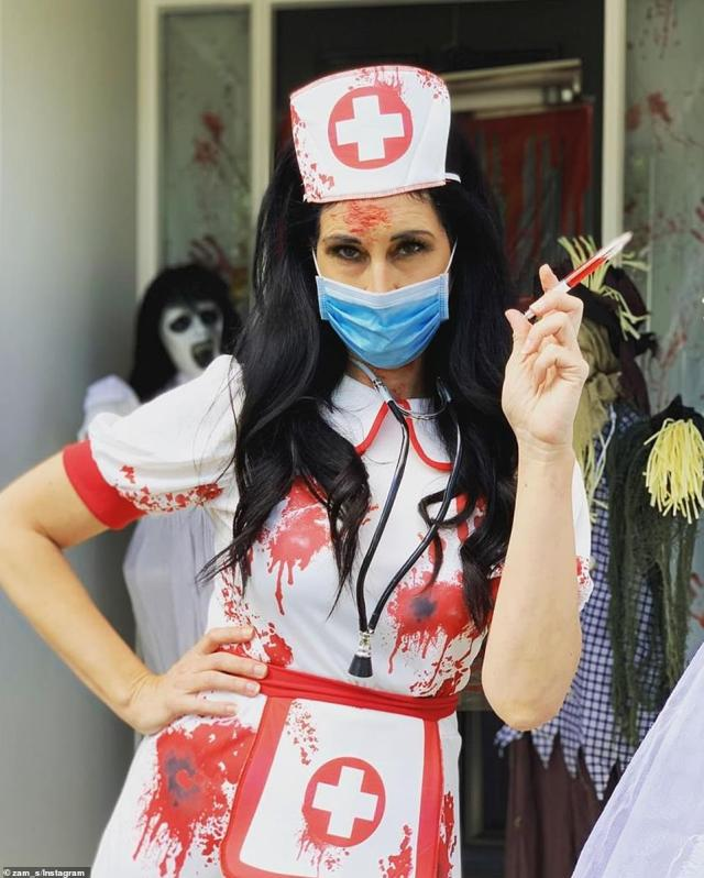 A blood-covered nurse with a face mask andstethoscope poses with a blood-filled syringe while others at the party dressed as a scarecrow and witch