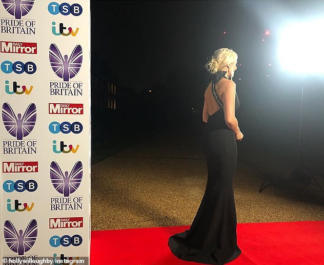 Glamorous: In one snap, she shied away from the camera to show off the gown's plunging back, brought together by a large bow at the nape of her neck