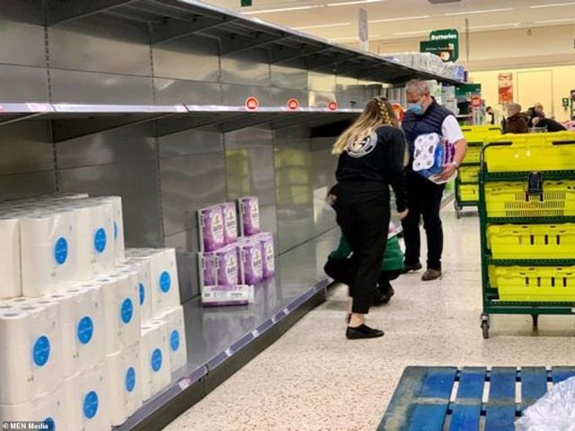 Shelves are emptied of toilet rolls at a Tesco store in Grimsby as swathes of customers race to bulk-buy household essentials on Sunday