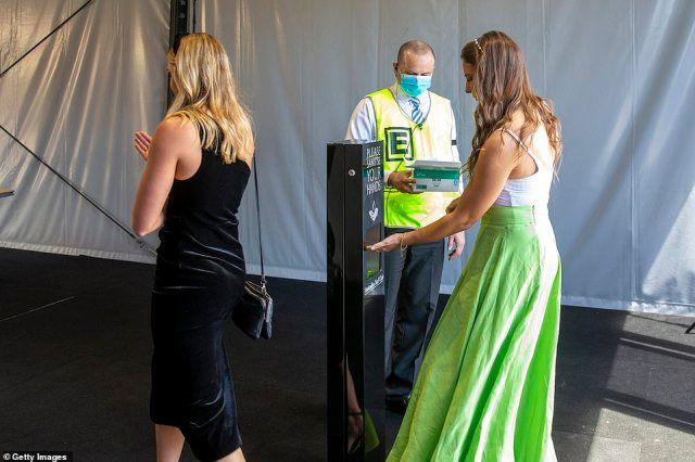 Racegoers sanitised their hands as they arrived at the track during Bentley Cup Day as part of coronavirus safety measures (pictured in Sydney)