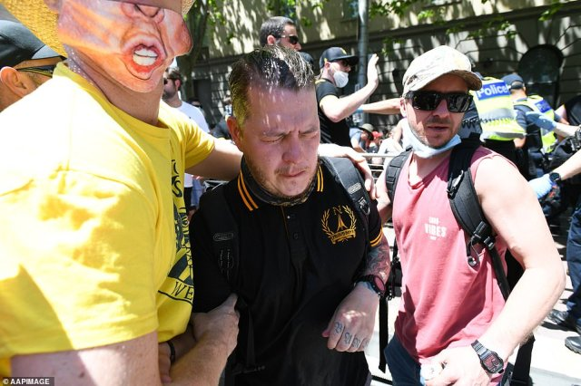 A protester affected by the capsicum spray is seen receiving help during the anti-lockdown protest in Melbourne
