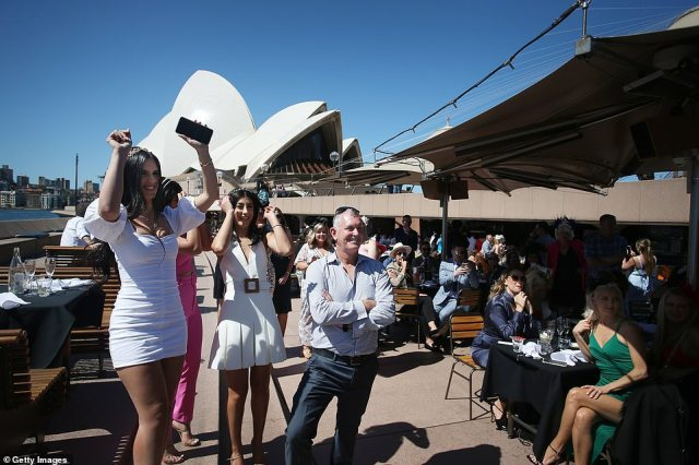 Punters in Sydney are seen celebrating the Melbourne Cup race in front of the Sydney Opera House at Sydney Harbour (pictured on Tuesday)