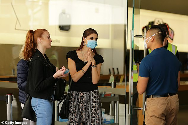 Dr Andrew Miller wants people in WA to start wearing masks to prevent COVID-19. Pictured: Apple staff speak with customers wearing face masks at the Perth store in May