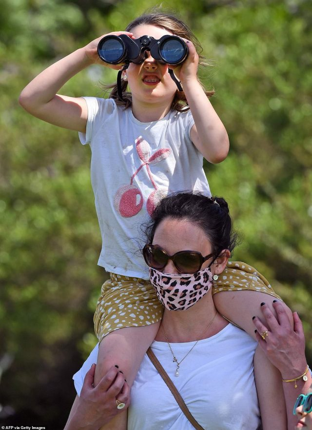 One young girl attempted to view the race through binoculars as she picnicked in a park overlookingFlemington Racecourse