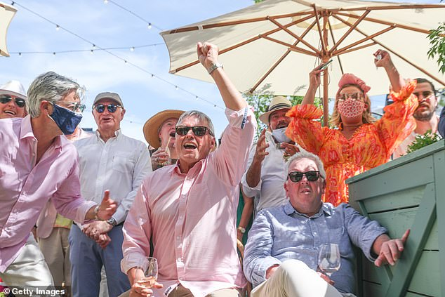 Patrons in Melbourne cheer on their horses during a televised screening of the race