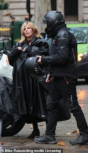 Arriving in style: Kate arrived via a motorbike and wore a long black mac to protect her from the rain