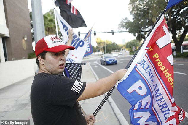 A supporter of President Donald Trump waves campaign flags near the Pinellas County Courthouse early voting polling station in Clearwater, Florida