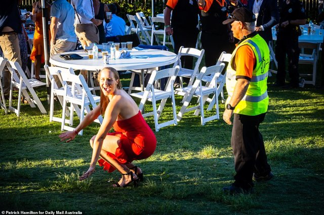 One woman was seen dropping to the ground as she playfully posed for a photograph in a tiny dress in front of a less than impressed steward