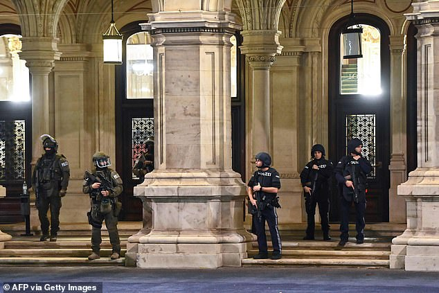 Armed policemen stand guard in front of the main entrance of the State Opera in the center of Vienna this evening following the shootings