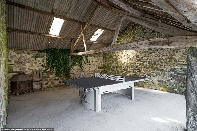 A table tennis area seen inside one of the barns, with wooden beams. Paddocks have the potential to expand the holiday business, with three former outbuildings being renovated into luxury cottages, subject to planning permission