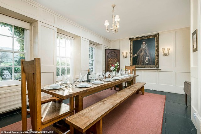 A dining table, which sits 14 people, with benches pictured inside the main house, with white-paned windows looking out onto the Welsh countryside, black stoned floors and a family portrait seen hanging on a wall at the head of the table