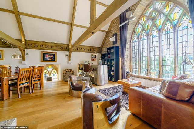 Pictured: The top floor of the property, which features stunning stained glass windows and the original vaulted ceilings