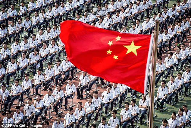 China is planning to update its school curriculum with content that boasts the country's 'heroic' fight against COVID-19. In this file photo, students attendthe 100th anniversary of the founding of Wuhan High School on the first day of the new semester on September 1