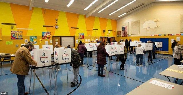 LANSING, MICHIGAN: Dozens of voters wearing masks cast their ballots at Willow School in Lansing