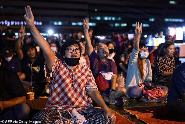 Pro-democracy protesters give the three-finger salute during protests against the Pornhub ban in Bangkok today