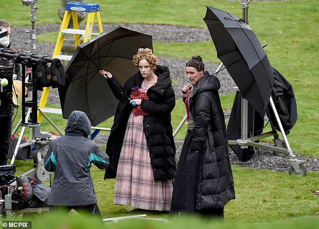 Keeping warm: During a break, Sophie and Suranne donned puffy coats and carried hot water bottles in their hands, while they used umbrellas to shield from the rain