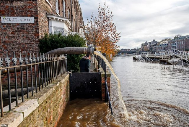 Water is pumped back into the Ouse after the river burst its banks following heavy rain with levels more than 12ft above those normally seen in the summer