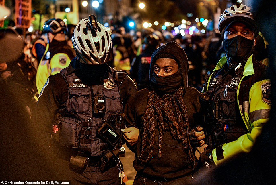 WASHINGTON DC: Police officers arrest a protester. There have been at least two arrests in the Capitol linked to the protests