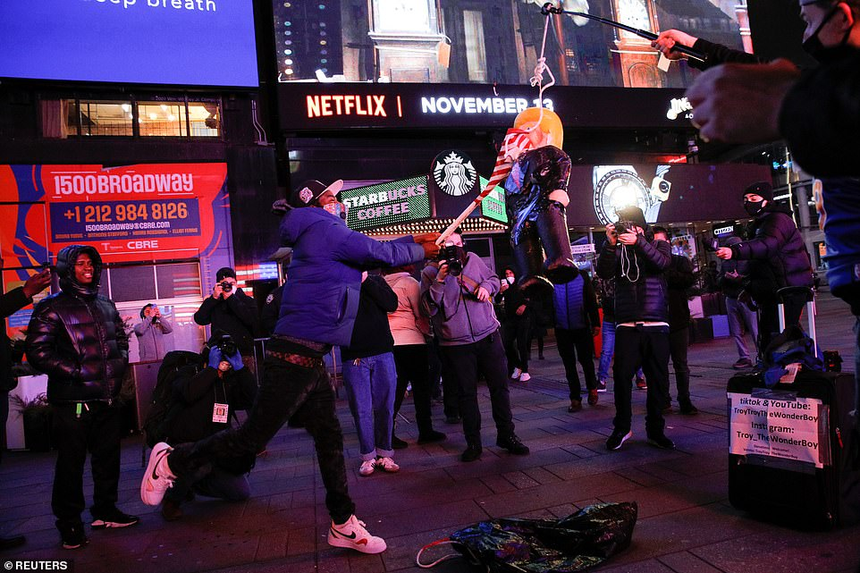 NYC: A protester uses an American flag to batter a Trumppiñata on Tuesday night in Times Square