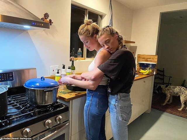 The film star pictured with her sister Whitney who wrapped her arms around Amber while she cooked in the kitchen in May