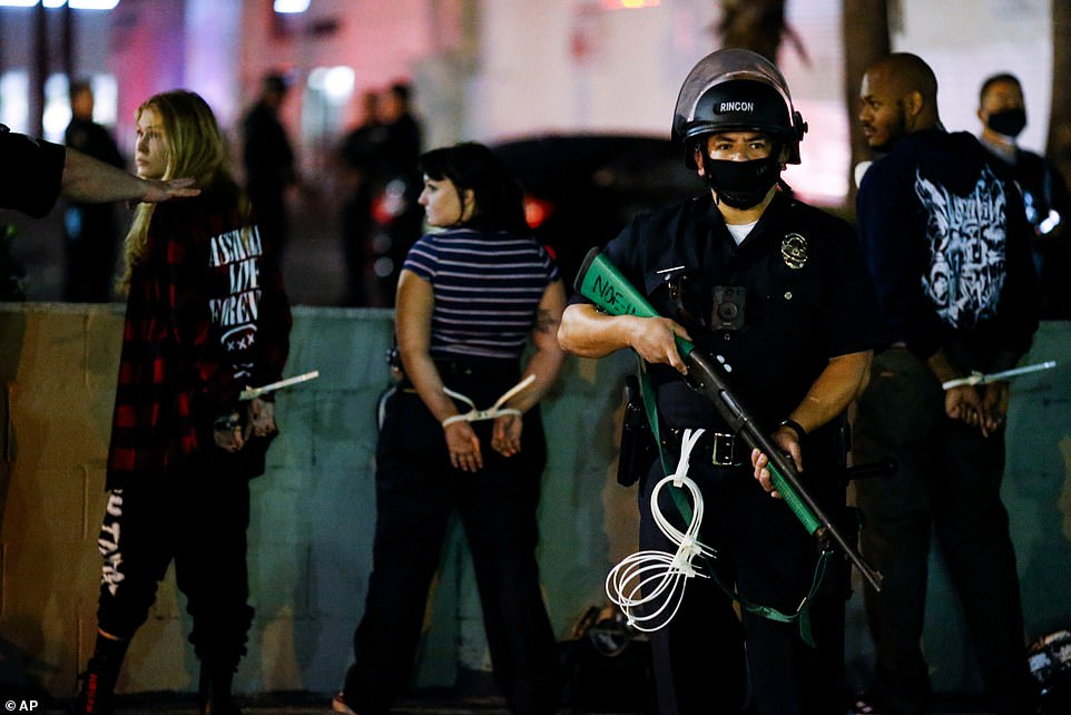 LOS ANGELES: Demonstrators are detained in the city election night while an armed police officer stands guard