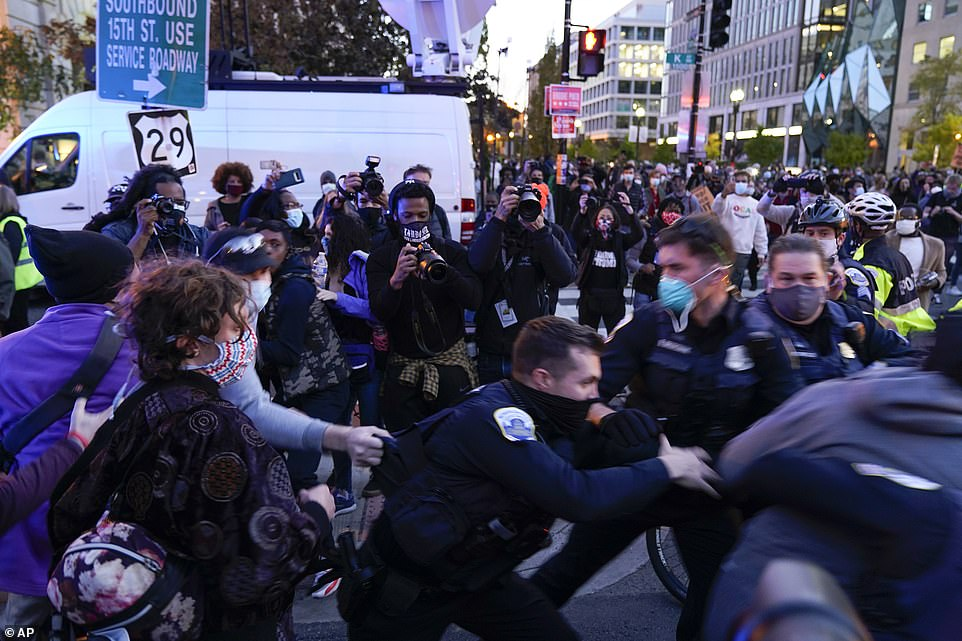 WASHINGTON DC: Police arrest a protester as people try to stop authorities moving the vehicle