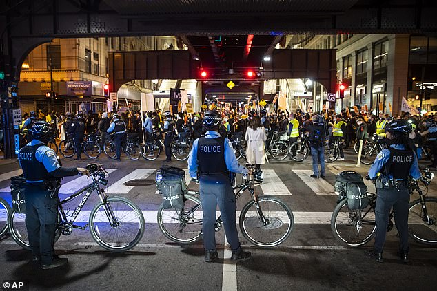 Chicago police officers keep watch as at least 1,000 protesters march through the Loop to demand every vote be counted