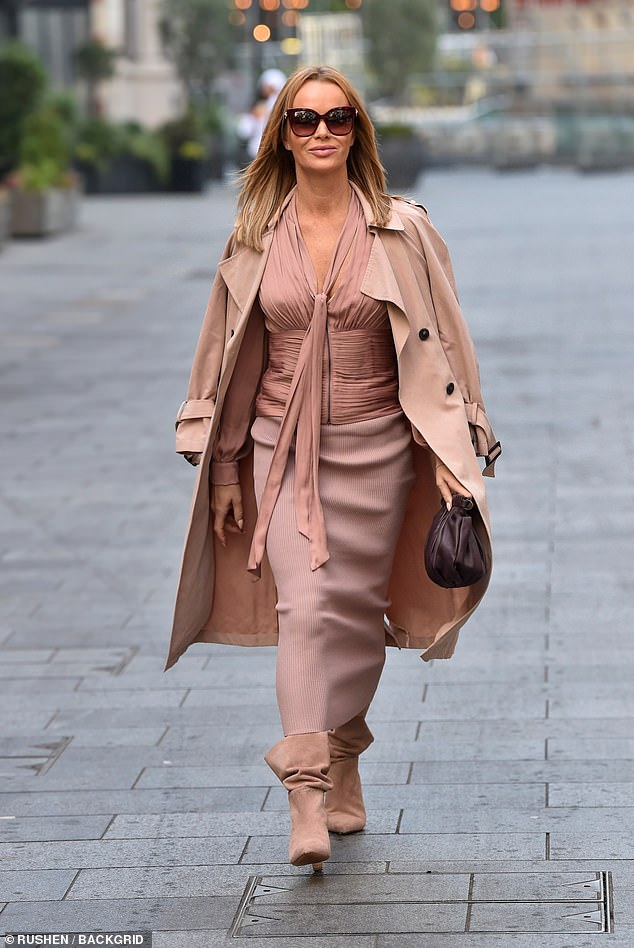 Pretty in pink:Amanda wrapped up for the cooler weather in a long ribbed midi skirt from Zara and draped a chic nude mac over her shoulders